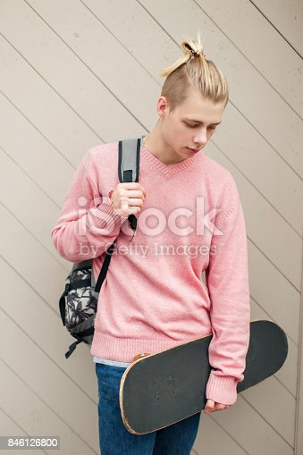 846124694istockphoto Handsome young man in a pink sweater with a backpack and skateboard near the wooden wall 846126800