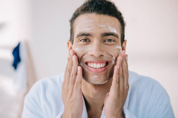 joven guapo en el albornoz aplicando espuma facial con las manos y sonriendo mientras mira la cámara - foto de stock