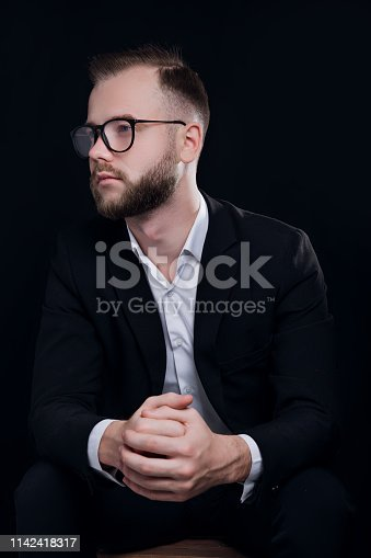 612752180istockphoto Handsome young man in black suit and glasses on black background 1142418317