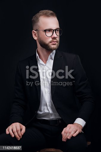 istock Handsome young man in black suit and glasses on black background 1142418537
