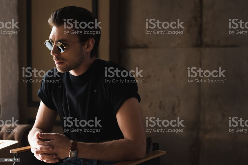 handsome young man in black t-shirt and sunglasses sitting on chair royalty-free stock photo