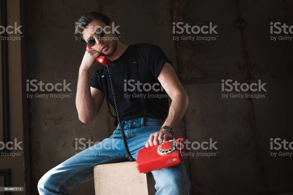 handsome young man in black t-shirt and sunglasses talking by retro wired red phone royalty-free stock photo