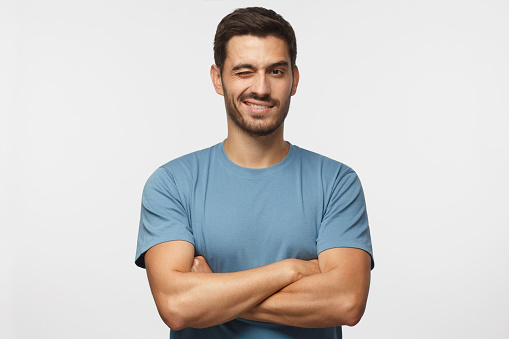 Handsome young man in blue t-shirt, with crossed arms smiling and winking, looking at camera isolated on gray background