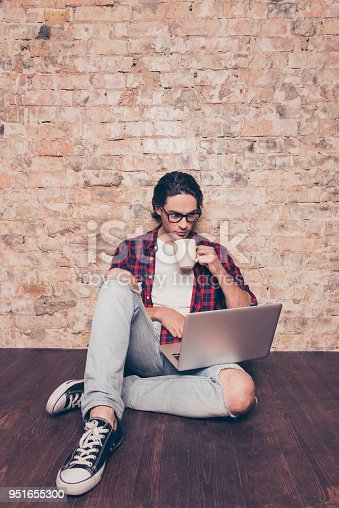 947303582 istock photo handsome young man in glasses sitting on floor with laptop and cup of coffee 951655300