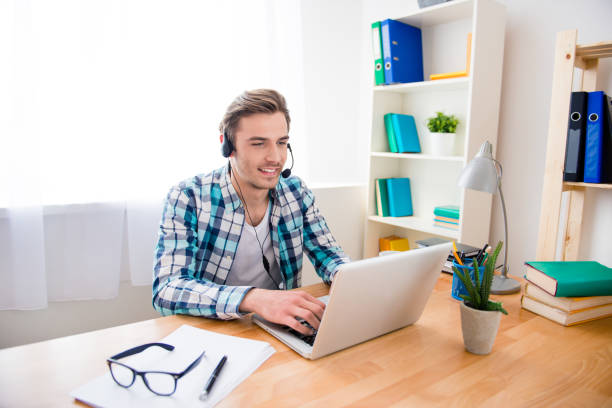 Handsome young man in headphones and laptop having conversation Handsome young man in headphones and laptop having conversation bingo caller stock pictures, royalty-free photos & images