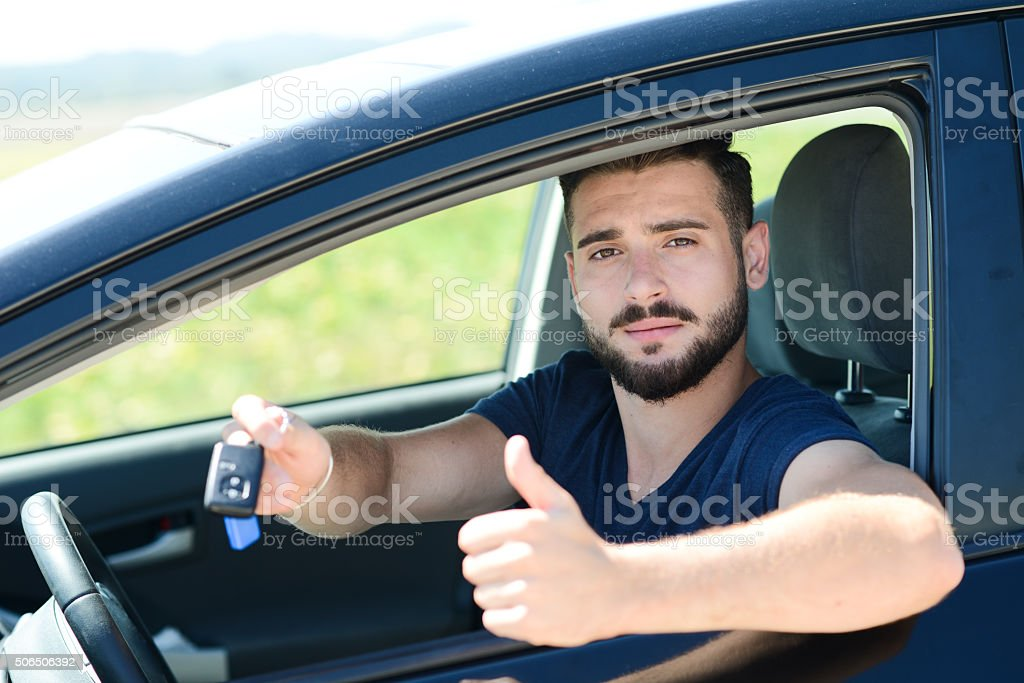 handsome and happy young man in car showing car keys