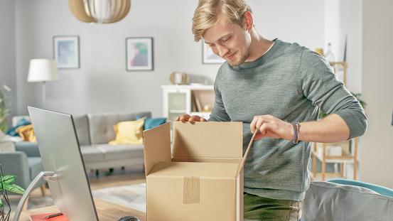 istock Handsome Young Man in Living Room Opening Cardboard Box Package With Interest. 1059208316