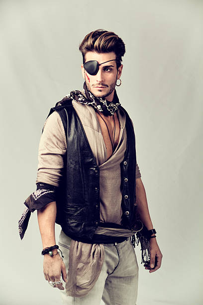Handsome Young Man in Pirate Fashion Outfit Good Looking Young Man in Pirate Fashion Outfit on Gray Background. Captured in Studio. costume eye patch stock pictures, royalty-free photos & images