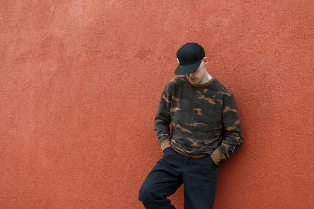 Handsome young man in stylish black cap in military fashionable shirt in trendy jeans rests standing near a vintage red wall in the city. American guy is relaxing outdoors on a summer day. Menswear. Handsome young man in stylish black cap in military fashionable shirt in trendy jeans rests standing near a vintage red wall in the city. American guy is relaxing outdoors on a summer day. Menswear. menswear stock pictures, royalty-free photos & images