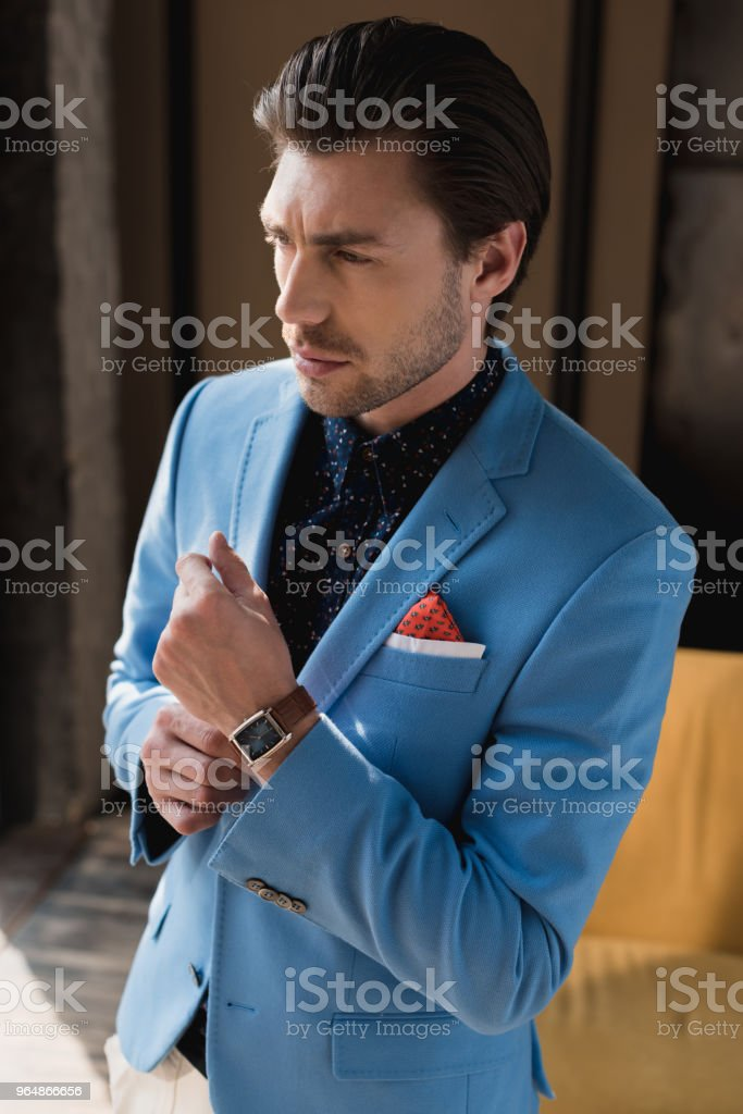 handsome young man in stylish blue jacket with wristwatch royalty-free stock photo