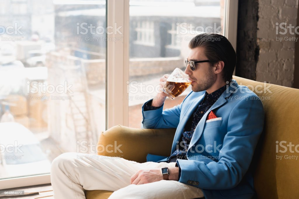 handsome young man in stylish suit sitting on couch and drinking beer royalty-free stock photo