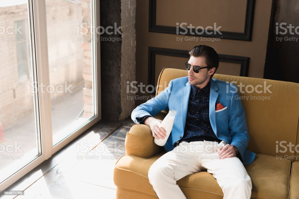 handsome young man in stylish suit sitting on couch with bottle of milk royalty-free stock photo
