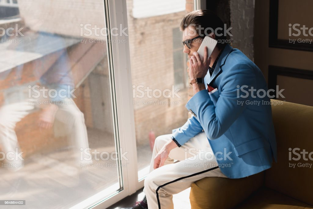 handsome young man in stylish suit talking by phone while sitting on couch royalty-free stock photo