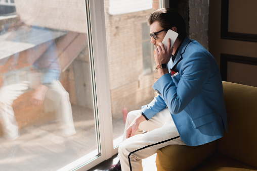 Handsome Young Man In Stylish Suit Talking By Phone While Sitting On Couch Stock Photo - Download Image Now