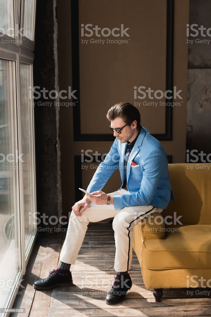 handsome young man in stylish suit using smartphone while sitting on couch royalty-free stock photo