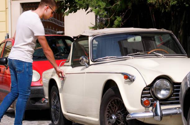 Jovem bonito em óculos de sol em pé na rua ao lado de um velho carro retrô urbano da cidade. Um cara abrindo e entrando em um bom velho temporizador carro branco, pronto para ir. Carro clássico, carro retrô e veículo conceito. - foto de acervo