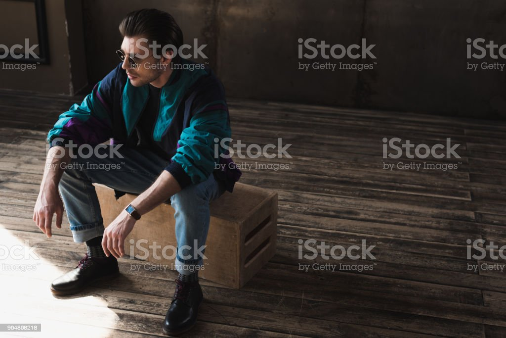 handsome young man in vintage windcheater sitting on wooden box in loft room royalty-free stock photo