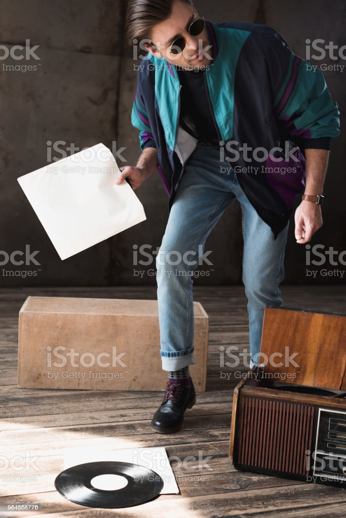 handsome young man in vintage windcheater with vinyl record player royalty-free stock photo