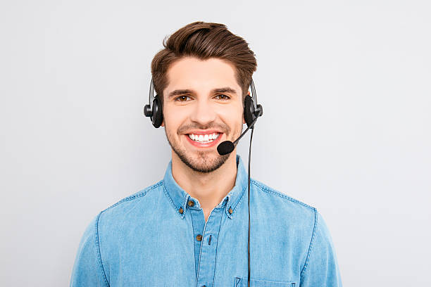 handsome young man in work in  call-centre with headphones stock photo