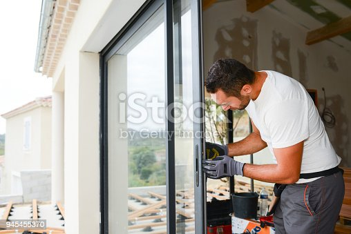945456460 istock photo handsome young man installing bay window in a new house construction site 945455370