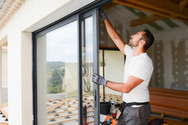 handsome young man installing bay window in a new house construction site stock photo
