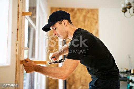 945456460 istock photo A handsome young man installing Double Sliding Patio Door in a new house construction site 1167036654