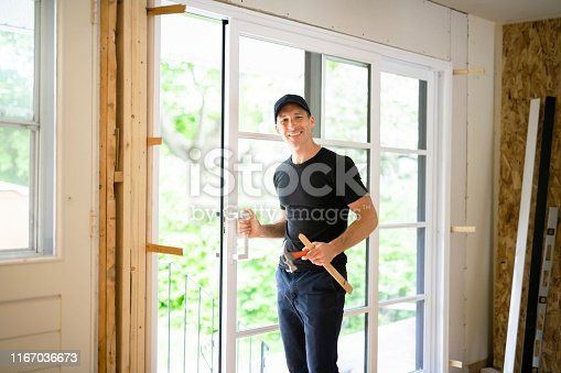945456460 istock photo A handsome young man installing Double Sliding Patio Door in a new house construction site 1167036673
