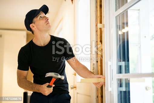 945456460 istock photo A handsome young man installing Double Sliding Patio Door in a new house construction site 1167036676