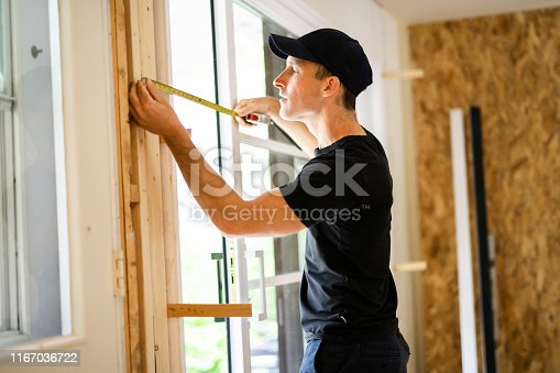 945456460 istock photo A handsome young man installing Double Sliding Patio Door in a new house construction site 1167036722