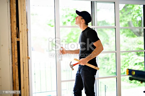 945456460 istock photo A handsome young man installing Double Sliding Patio Door in a new house construction site 1167036723