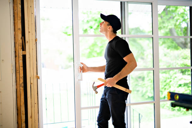 A handsome young man installing Double Sliding Patio Door in a new house construction site stock photo