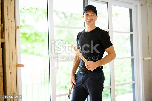 945456460 istock photo A handsome young man installing Double Sliding Patio Door in a new house construction site 1167036727