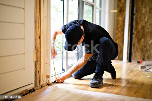 945456460 istock photo A handsome young man installing Double Sliding Patio Door in a new house construction site 1167036746