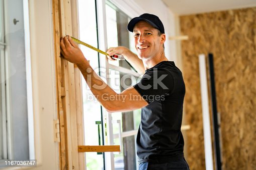 945456460 istock photo A handsome young man installing Double Sliding Patio Door in a new house construction site 1167036747