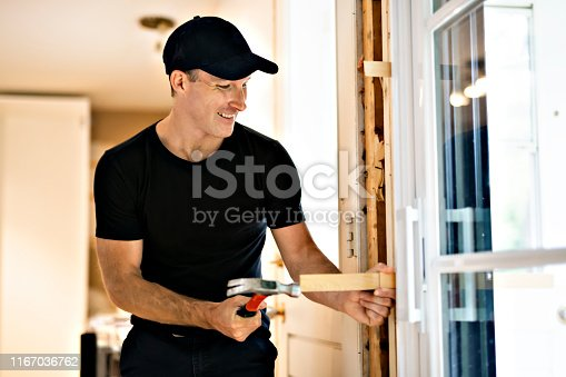 945456460 istock photo A handsome young man installing Double Sliding Patio Door in a new house construction site 1167036762
