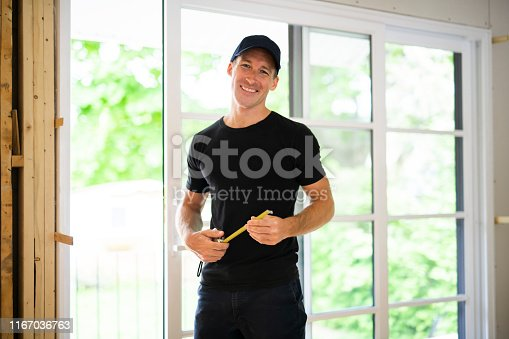 945456460 istock photo A handsome young man installing Double Sliding Patio Door in a new house construction site 1167036763