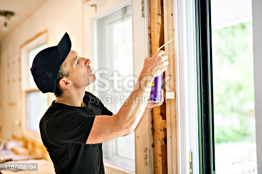 945456460 istock photo A handsome young man installing Double Sliding Patio Door in a new house construction site 1167036764