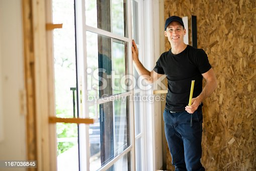 945456460 istock photo A handsome young man installing Double Sliding Patio Door in a new house construction site 1167036845