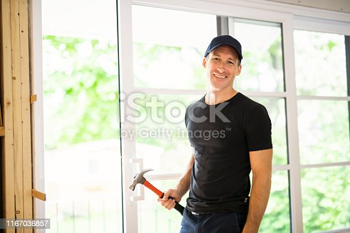 945456460 istock photo A handsome young man installing Double Sliding Patio Door in a new house construction site 1167036857