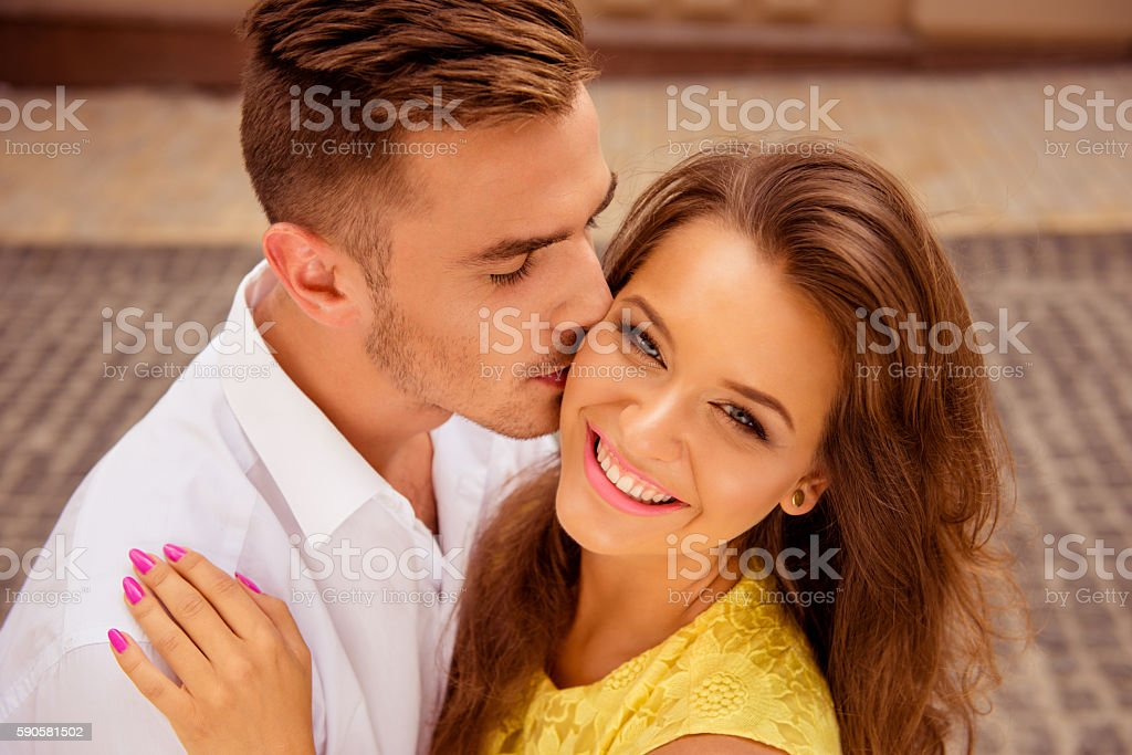 handsome young man kissing his beloved's cheek stock photo
