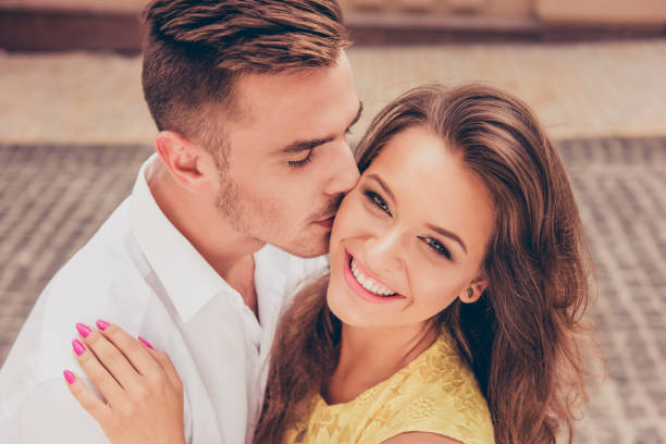 handsome young man kissing his beloved's cheek handsome young man kissing his beloved's cheek pecking stock pictures, royalty-free photos & images