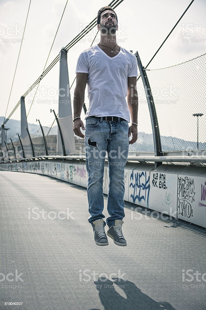 Handsome young man levitating in mid-air outdoors stock photo