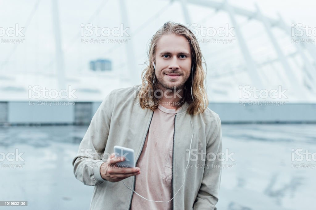 handsome young man listening music with earphones and smartphone on...