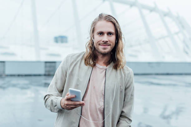 handsome young man listening music with earphones and smartphone on street and looking at camera handsome young man listening music with earphones and smartphone on street and looking at camera medium length hair stock pictures, royalty-free photos & images