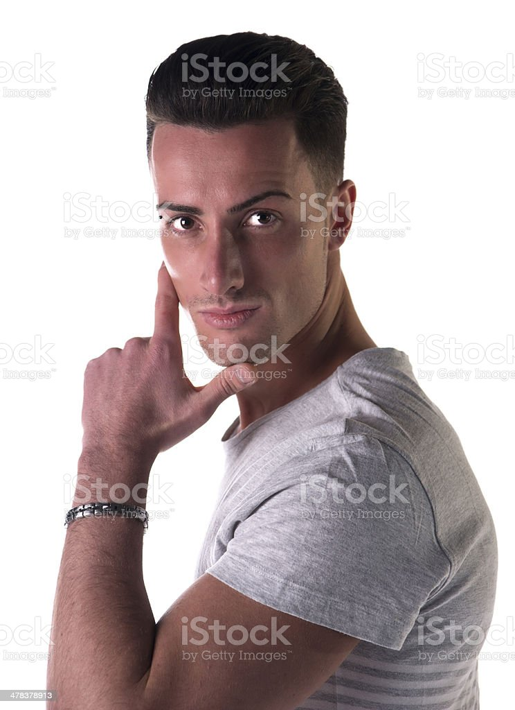Handsome young man looking at camera, hand on his chin stock photo