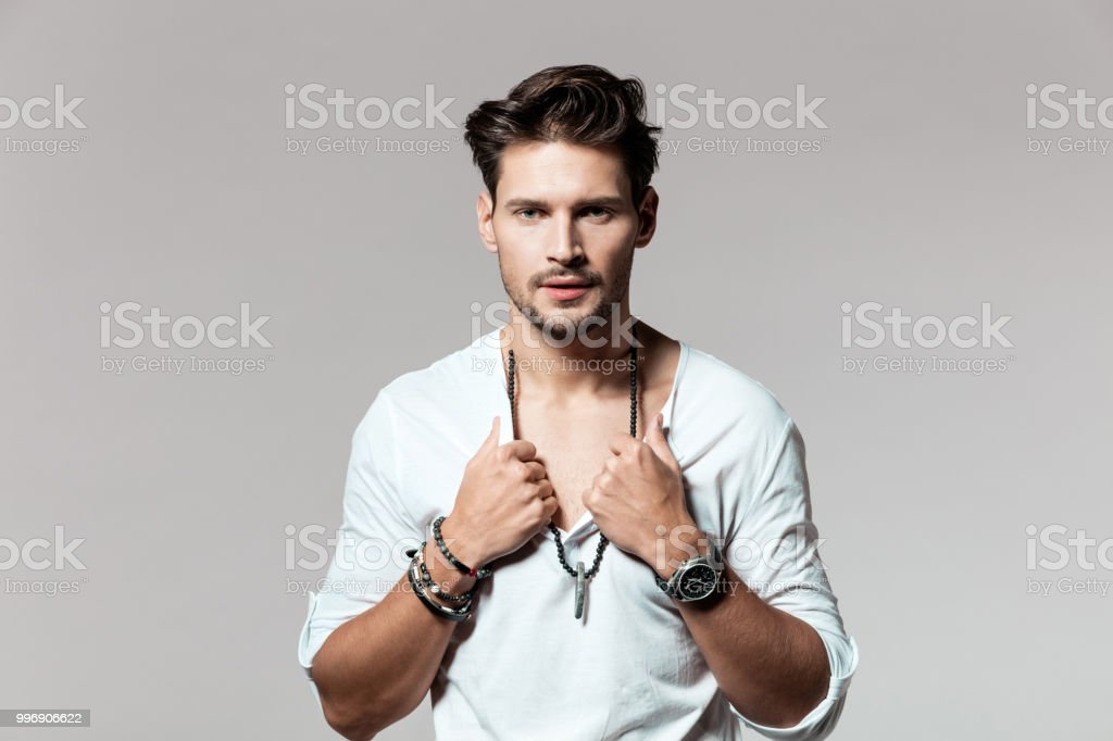 Handsome young man looking at camera Portrait of handsome young man looking at camera on grey background 25-29 Years Stock Photo
