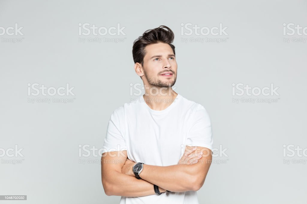 Handsome young man looking at copy space Portrait of handsome young man looking away with his arms crossed smiling on grey background 25-29 Years Stock Photo