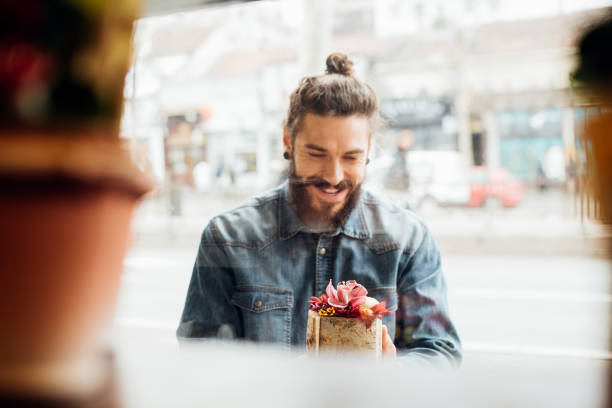 Handsome young man looking at flowers Handsome young man looking at flowers in front of flower store man bun stock pictures, royalty-free photos & images
