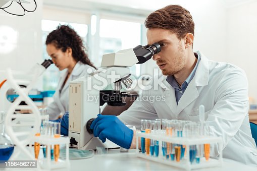 istock Handsome young man looking into the microscope 1156456272
