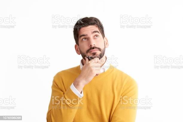 Photo of Handsome young man looking thoughtfully at isolated white background with copy space